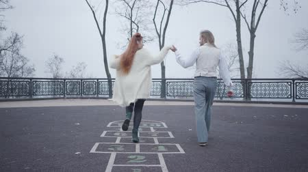 dvojitý : Young Caucasian man in elegant clothes holding his girlfriends hand as she jumping on the hopscotch game drawn on the asphalt. Carefree millennial couple resting outdoors Dostupné videozáznamy