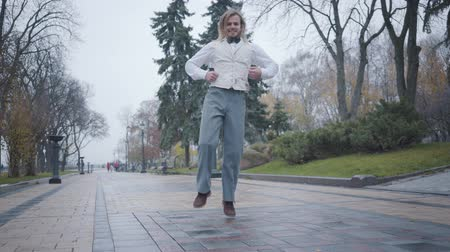 charisma : Cheerful young Caucasian boy in elegant white shirt, vest, and plaid bow tie dancing in the city park. Funny Caucasian man having fun in the autumn day outdoors