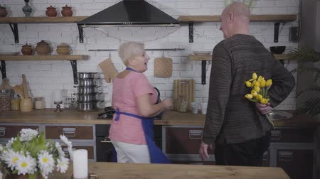 eternal : Back view of mature bald Caucasian senior man approaching his wife and presenting her bouquet of yellow tulips. Mature woman in pink T-shirt getting surprise from her husband. Romance, eternal love Stock Footage
