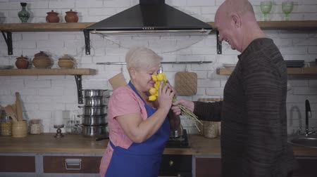eterno : Cheerful mature Caucasian bald man giving bouquet of yellow tulips to his adorable wife. Blond Caucasian woman in pink T-shirt getting surprise while cooking at the kitchen. Romance, eternal love Filmati Stock