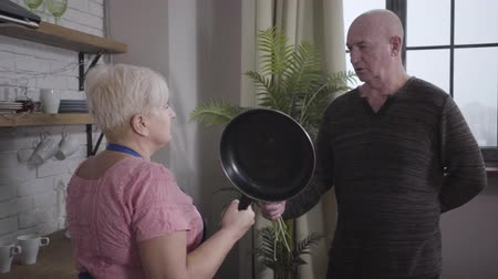 eternal : Portrait of mature Caucasian baldheaded man apologising with a bouquet of yellow flowers. Angry wife threatening him with frying pan. Wife educating her guilty spouse. Retirees having fun