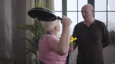eterno : Funny Caucasian grandma threatening her husband with frying pan. Smiling mature baldheaded man defending himself with a bouquet of yellow tulips. Wife educating her guilty spouse. Retirees having fun
