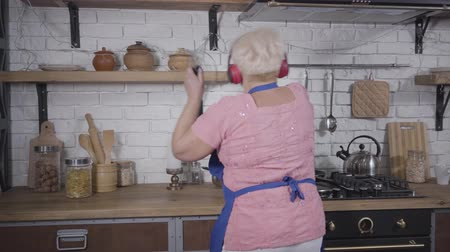 piada : Back view close-up of positive senior Caucasian woman dancing while cooking at the kitchen. Energetic dance of mature lady in headphones. Cheerful retiree enjoying life after retirement Vídeos