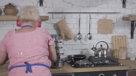 piada : Happy smiling senior Caucasian woman in headphones dancing at the kitchen holding saucepan. Energetic dance of mature lady . Cheerful retiree enjoying life after retirement Stock Footage