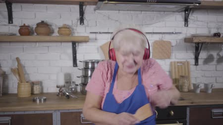 zavřít : Close-up of positive senior Caucasian woman dancing and emotionally gesturing. Funny old woman in headphones singing and dancing at the kitchen. Mature cheerful retiree enjoying life after retirement