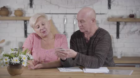 liquidação : Mature Caucasian baldheaded man blaming his wife because of overspending. Senior couple dealing with bills. Spouses settling their income and expenses. Financials, retirees, payouts