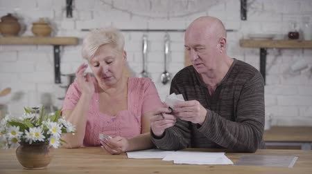 belasting : Portrait of senior Caucasian sad woman looking through bills. Husband blaming his wife because of overspending. Spouses settling their income and expenses. Financials, retirees, payouts Stockvideo