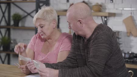 liquidação : Side view of old Caucasian man showing bills to his beautiful wife. Senior lady ashanmed because of overspending. Wife spending family budget, retirement Stock Footage
