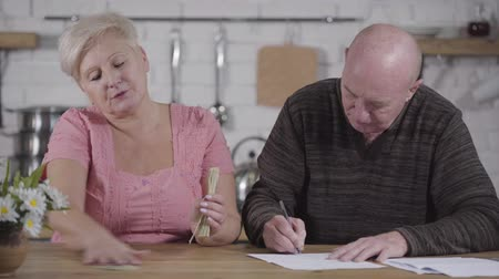 liquidação : Close-up of senior Caucasian husband and wife settling their finances. Woman holding cash, man writing down. Old spouses settling their financials