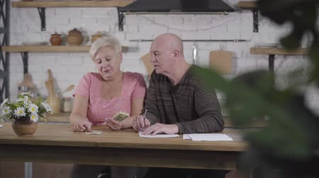 belasting : Mature Caucasian husband and wife settling their income and expenses. Woman counting cash, man writing down budget. Old spouses settling their financials