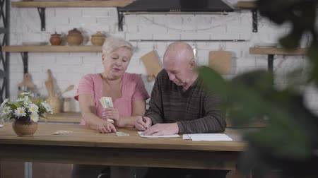 liquidação : Portrait of senior Caucasian couple counting money. Husband and wife settling their income and expenses. Woman holding cash, man writing down budget. Old spouses settling their financials