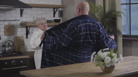 örök : Back view of funny baldheaded Caucasian man dancing in front of mature wife and opening his bathrobe. Senior Caucasian woman with coffee cup looking at him condescendingly