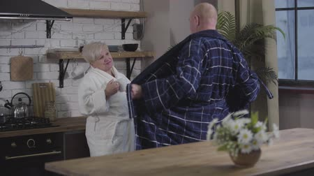 eternal : Positive mature Caucasian man dancing in front of wife and opening his bathrobe. Blond woman with coffee cup looking at him with love and hugging. Retirees having fun at home