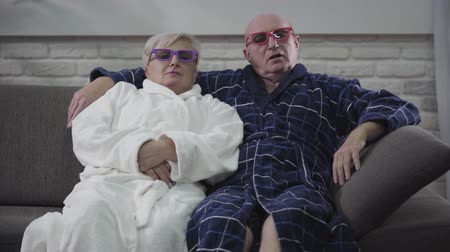 örök : Cheerful Caucasian senior couple sitting on sofa and moving depending on 3D movie. Joyful husband and wife resting at home after retirement. Happiness, enjoyment, fun, eternal love