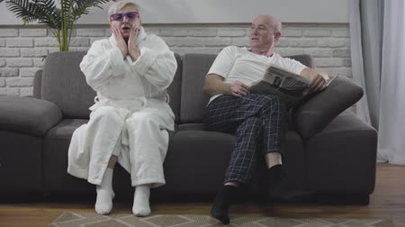 газета : Mature blond Caucasian woman in white bathrobe sitting on sofa and emotionally watching 3D TV. Her baldheaded husband sitting with newspaper and talking to wife. Seniors resting at home
