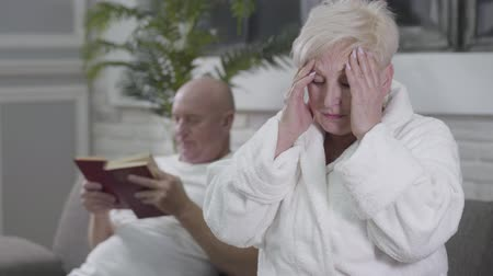 örök : Portrait of sad Caucasian woman with headache sitting in white bathrobe and rubbing temples. Her husband sitting at the background and reading book. Aging, healthcare, eternal love, care