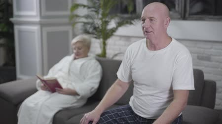coming home : Concentrated senior bald man sitting on couch and watching TV when suddenly having heartache. His blond Caucasian wife putting aside book and coming to husband from background. Medicine, health, care Stock Footage