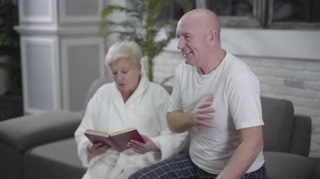 coming home : Old Caucasian bald man talking with his blond beautiful wife. Husband suddenly having heartache, woman putting aside book and coming to husband. Medicine, health, care Stock Footage