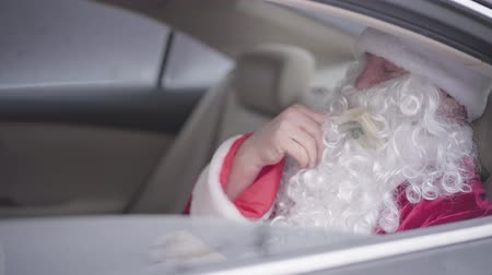 white out : Side view of old Santa Claus sitting in the car on back seat and counting pack of dollars. Christmas, holiday, bad Santa. Rich guy, after holiday Stock Footage
