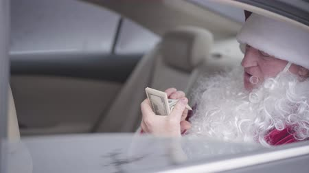 yanliŞ : Old Santa Claus sitting in the car on back seat, taking off the false beard, licking finger and counting pack of dollars. Christmas, holiday, bad Santa. Rich guy, after holiday Stok Video