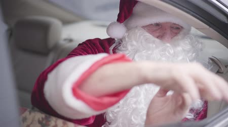 yanliŞ : Bearded Santa giving present boxes to an unrecognizable child from the car window. Old Santa Claus sitting in the car on the back seat. Christmas, holiday, gifts concept