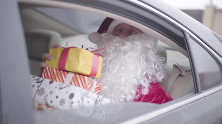 świety mikołaj : Old Santa Claus opening car window and winking. Bearded Santa sitting in the car on back seat with present boxes. Christmas, holiday, gifts concept Wideo