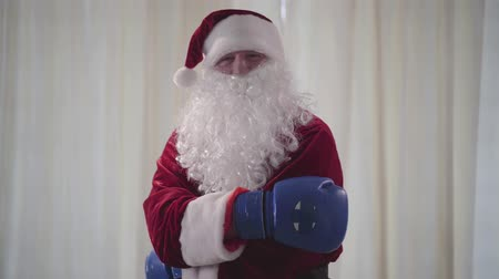 yanliŞ : Bearded funny Santa Claus in blue boxing gloves wants to fight. Old man waving his hands threateningly. Christmas, holiday, bad Santa character Stok Video