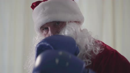 negatividade : Bearded funny Santa Claus in blue boxing gloves wants to fight close-up. Old man threateningly punching air looking in the camera. Christmas, holiday, bad Santa