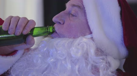 leftover : Side view of tired old man in Santa Claus costume drinking beer and watching TV. Close-up portrait of bad Santa Claus. Alcoholism, depression, negativism