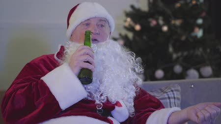 leftover : Close-up of sad Caucasian man in Santa Claus costume chewing and drinking beer. Bad Santa Claus sitting on couch next to the Christmas tree. Alcoholism, depression, negativism