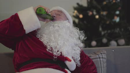świety mikołaj : Old man with a false white beard in the costume of Santa Claus drinking beer sitting on the sofa watching TV at home. Bad Santa. Alcoholism, depression, negativism, loneliness Wideo