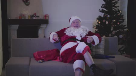 świety mikołaj : Portrait of mature Caucasian man in Santa Claus clothes sitting with beer and watching TV. Bad alcoholic Santa resting on couch at the background of Christmas tree Wideo