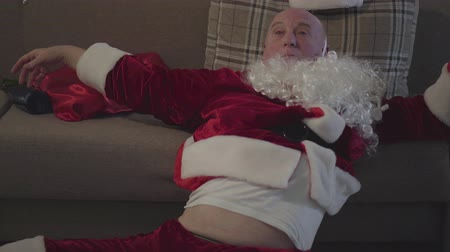 christmas background : Drunk old man with false white beard in the costume of Santa Claus falling out of bed at home and confused looking around. Bad Santa. Alcoholism, depression, negativism, loneliness Stock Footage