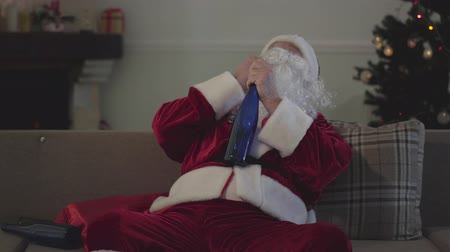 świety mikołaj : Dead drunk senior man in Santa Claus costume sitting on couch and drinking. Lonely Caucasian guy spending holidays alone. Bad Santa, alcoholism, negativism