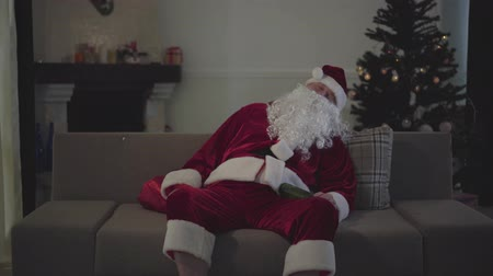 świety mikołaj : Portrait of mature Caucasian man in Santa Claus costume sleeping on the couch holding the bottle of beer. Old guy spending holidays alone at home. Bad santa, loneliness, depression, alcohol addiction Wideo
