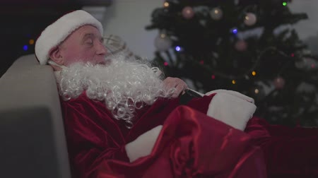 yanlış : Side view portrait of mature Caucasian man in Santa Claus costume sleeping at the background of Christmas tree. Tired male Santa resting after difficult working day