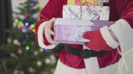 świety mikołaj : Unrecognizable man in the costume of Santa Claus stretching out gift box in front of the New Year tree. The man holding present boxes. Concept of happy holidays, traditions, Christmas