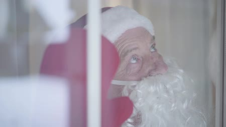 świety mikołaj : Close-up face of mature Caucasian man in Santa Claus costume waving hand and looking up. Shooting through window glasws. Concept of happy holidays, traditions, Christmas