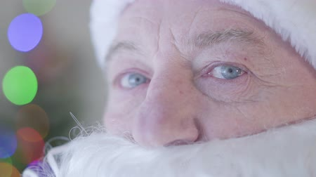 świety mikołaj : Close-up eyes of mature Caucasian Santa Claus looking away with tears on his eyes. Concept of sadness, sadness, lack of festive mood