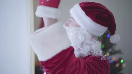 świety mikołaj : Close-up of senior Caucasian man with false beard in Santa Claus costume shaking his head and waving hand. Concept of happy holidays, traditions, Christmas Wideo