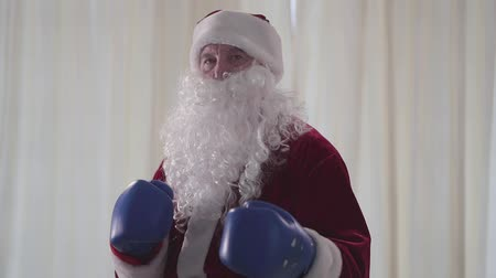 świety mikołaj : Portrait of bearded funny Santa Claus in blue boxing gloves wants to fight close-up. Old man threateningly looking in the camera. Christmas, holiday, bad Santa concept