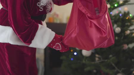 świety mikołaj : Unrecognizable man in the costume of Santa Claus shakes gifts from bag to floor in front of the decorated New Year tree. Concept of happy holidays, traditions, Christmas. Slow motion Wideo