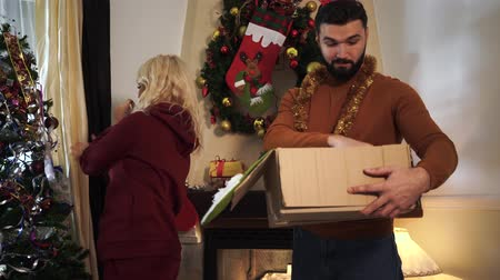 krans : Blond Caucasian woman decorating Christmas tree as bearded man choosing garlands in box. Young couple spending weekend together on New Years eve