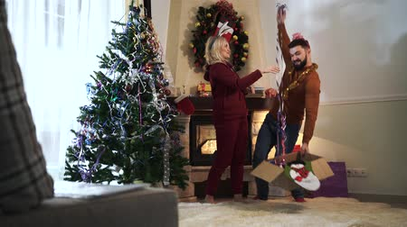 headband : Joyful Caucasian man and woman having fun at home on New Years eve. Husband and wife hanging Christmas decorations on each other. Happiness, joy, holidays