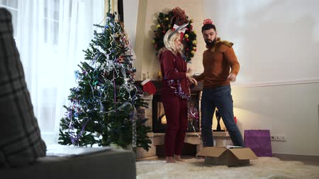 díszített : Young Caucasian girl with blond hair putting Happy New Year headband on husbands head. Cheerful couple dancing at home next to the decorated Christmas tree. Happy family on holidays