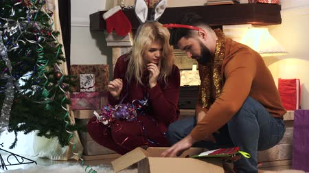 appendere : Close-up portrait of Caucasian husband and wife decorating house on New Years eve together. Woman standing up to hang New Year ball on Christmas tree, happy man sitting and dancing