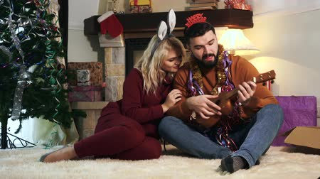 coelho : Portrait of young Caucasian woman in bunny ears headband and man in happy new year headband sitting on carpet in front of Christmas tree. Husband playing ukulele for lovely wife on New Years eve Stock Footage
