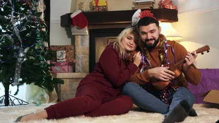 saç bantı : Young blond woman holding her head on husbands shoulder and listening to him singing and playing ukulele. Happy spouses resting after decoration of house on New Years eve. Holidays season