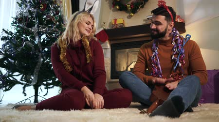coelho : Cheerful husband and wife sitting in front of decorated Christmas tree and dancing. Happy Caucasian man and woman resting at home on New Years eve. Holidays, celebration
