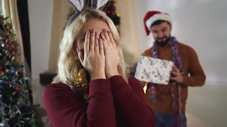 закрытыми глазами : Close-up of young blond Caucasian woman with eyes closed standing at the foreground. Defocused bearded man in Christmas hat holding gift box at the background. New Years eve, holidays season